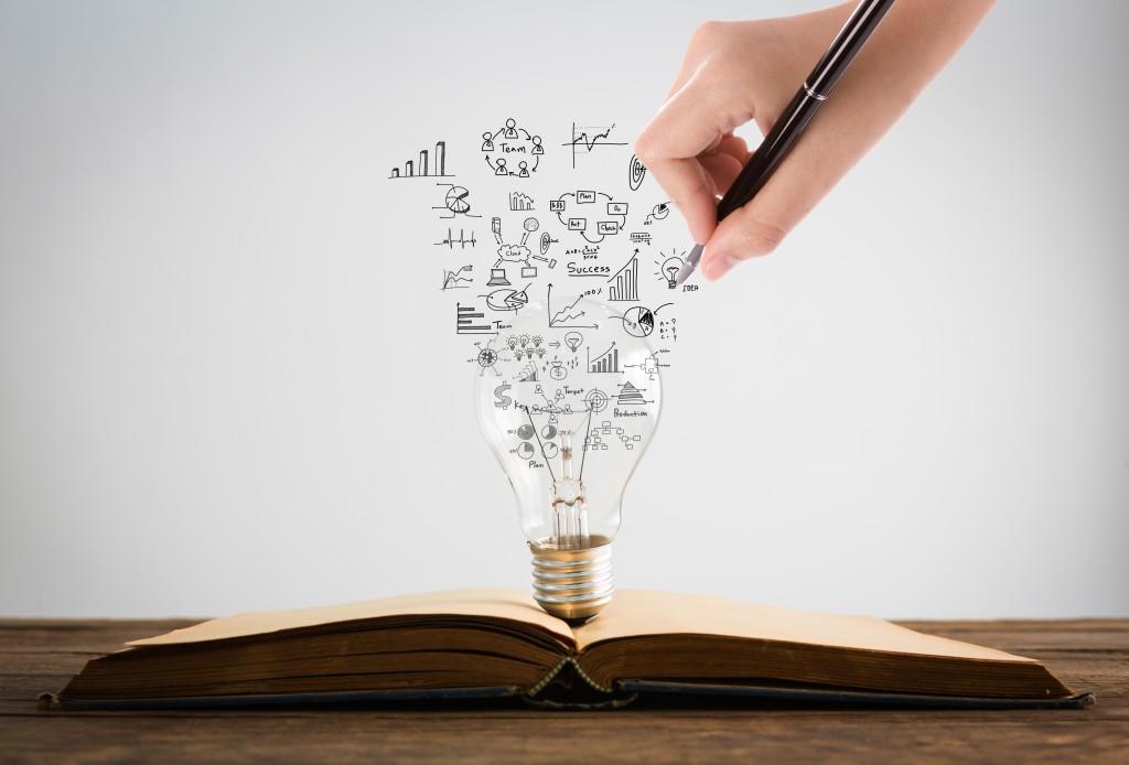 lampada de ideias saindo de um livro impresso